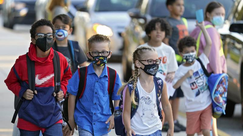 In this Tuesday, Aug. 10, 2021, file photo, students, some wearing protective masks, arrive for...