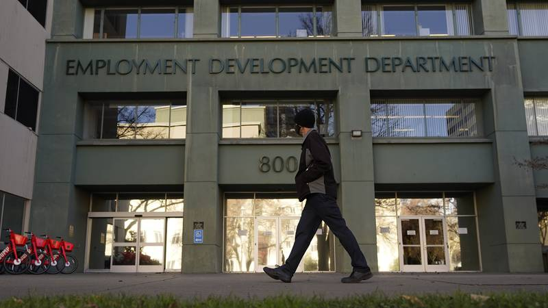 FILE - In this Dec. 18, 2020, file photo, a person passes the office of the California...